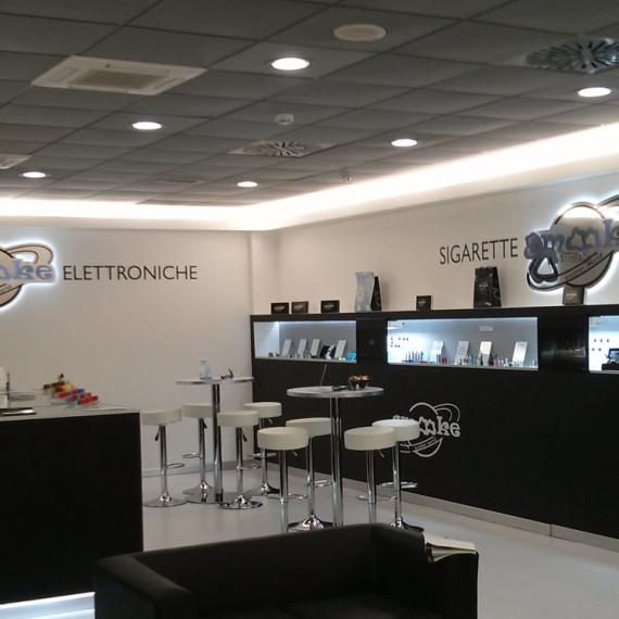 Immagine interna del negozio smooke nell'aereoporto di Torino. Insegna, desk reception e fronte espositivo e vendita, area salotto prova e attesa.