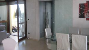 Progetto di interni per una residenza privata. Vista della zona pranzo. dettaglio del tavolo e della porta scorrevole in vetro.